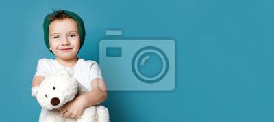 Fototapeta Little boy in green hat hold polar bear toy smiling. International day of polar bear concept