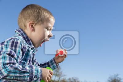 Little boy is blowing a soap bubbles