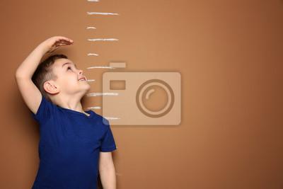 Fototapeta Little boy measuring his height on color background