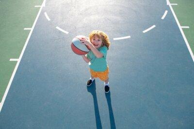Fototapeta Little boy playing basketball. Child sport activity. Kids basketball school.