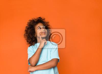 Fototapeta Little daydreamer. Girl holding finger on chin and looking away