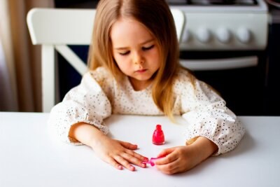 Fototapeta Little girl paints her nails with pink nail polish. Cute toddler girl  playing with colorful nail polish doing manicure. Cosmetics and beauty concept.