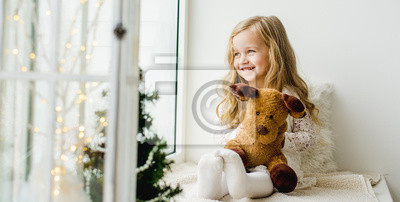 Fototapeta little girl with a plush deer sitting on the window. A child looks out the window and is waiting for Christmas, Santa Claus