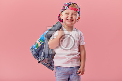 Fototapeta Little serious fashionable toddler boy in denim clothes and trendy cap. Isolated on pink background