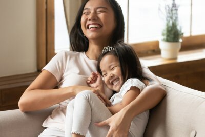 Fototapeta Lively asian young mother tickling little daughter enjoy free time active weekend together, wearing casual comfortable home clothes kid girl tiara accessory, beautiful happy family having fun concept