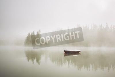 Fototapeta Łódź na jeziorze w porannej mgle.