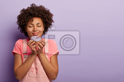 Fototapeta Lovely Afro woman holds delicious donut, smells with pleasure, likes eating sweets, has good appetite, closes eyes, wears pink t shirt and dungarees, being real sweet tooth. Unhealthy eating concept