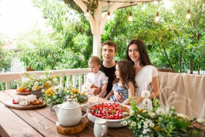 Fototapeta Loving family with kids sitting at table with delicious desserts and flowers during breakfast in countryside in summer