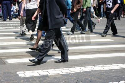 Ludzie przechodzą przez ulicę w mieście