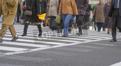 Ludzie przechodzą przez ulicę w widoku na miasto.