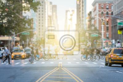 Fototapeta Ludzie przechodzący przez ruchliwy skrzyżowanie między ruchem na 3rd Avenue i 10th Street na Manhattanie w Nowym Jorku z blaskiem słońca w tle