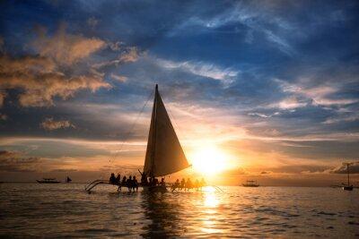 Fototapeta Ludzie siedzą na łodzi na oceanie i patrząc zachód słońca