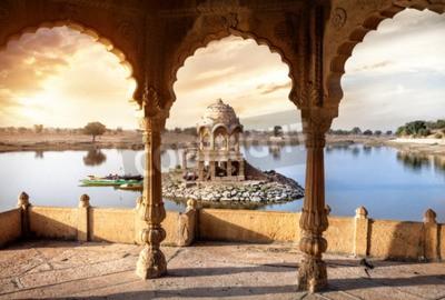 Fototapeta Łuki i świątynia w Gadi Sagar jeziorze o zachodzie słońca niebo w Jaisalmer, Radżastan, Indie