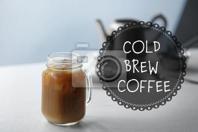 Lukrowa kawa w szklanym słoju na białym drewnianym stole