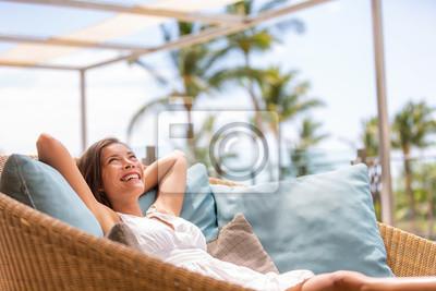 Fototapeta Luxury hotel home living woman relax enjoying sofa furniture of outdoor patio. Beautiful young multiracial Asian girl relaxing day dreaming for rich early retirement in getaway tropical house.