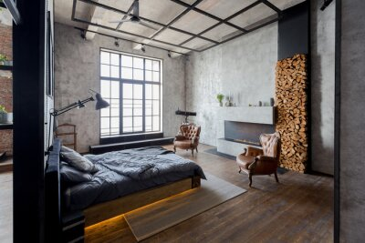 Fototapeta luxury studio apartment with a free layout in a loft style in dark colors. Stylish modern kitchen area with an island, cozy bedroom area with fireplace and personal gym