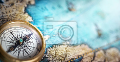 Fototapeta Magnetic compass on world map.Travel, geography, navigation, tourism and exploration concept background. Macro photo. Very shallow focus.