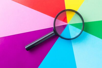 Fototapeta Magnifying glass on multi-colored sheets of paper. Search for diversity color combinations. The concept of finding a variety of choices.