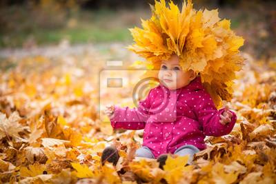 Fototapeta Małe dziecko jest gra i siedzi w opadłych liści w parku jesienią. Dziecko jest w wielkim wieniec z liści. Dziewczyna jest ubrana w ciepły kapelusz, kurtka.