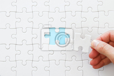 Fototapeta male hand putting the last piece in the puzzle.