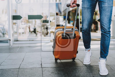 Fototapeta Male is carrying luggage in hall before trip