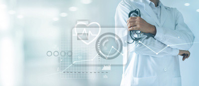Fototapeta Male medicine doctor with stethoscope in hand standing confidently on hospital background