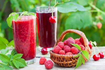 Fototapeta Malina i kwaśny sok wiśniowy na stole rustykalnym
