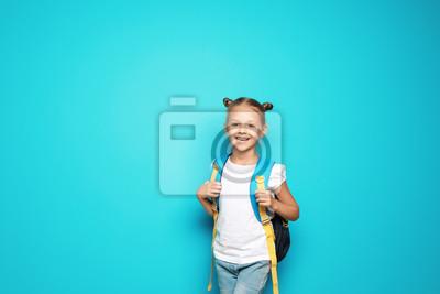 Fototapeta Mały dziecko w wieku szkolnym z plecakiem na koloru tle