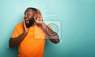 Fototapeta Man hears a secret notice. Concept of curiosity and gossip. Amazed expression