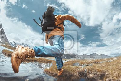 Fototapeta Man hiker jumps across water in mountain area