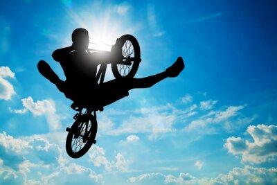Fototapeta Man jumping on bmx bike performing a trick against sunny sky