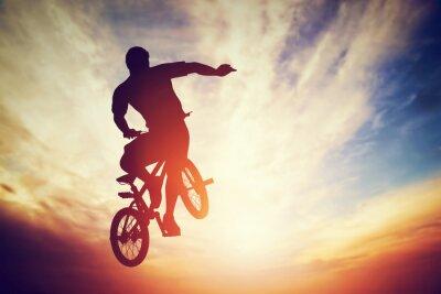 Fototapeta Man jumping on bmx bike performing a trick against sunset sky