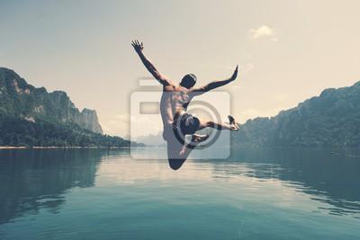 Fototapeta Man jumping with joy by a lake