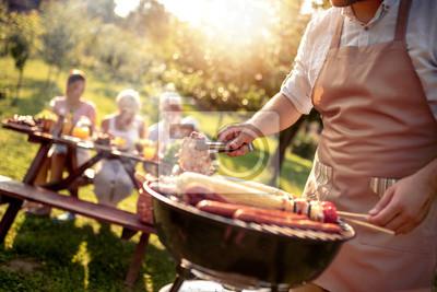 Fototapeta Man preparing food on garden barbecue