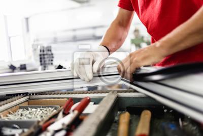 Fototapeta Manual worker assembling PVC doors and windows. Manufacturing jobs. Selective focus. Factory for aluminum and PVC windows and doors production.