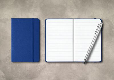Fototapeta Marine blue closed and open lined notebooks with a pen on concrete background