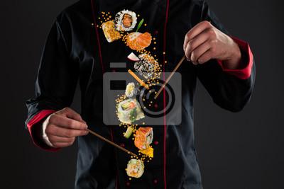 Fototapeta Master chef holding chopsticks with flying sushi
