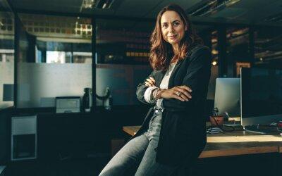 Fototapeta Mature businesswoman sitting on her desk