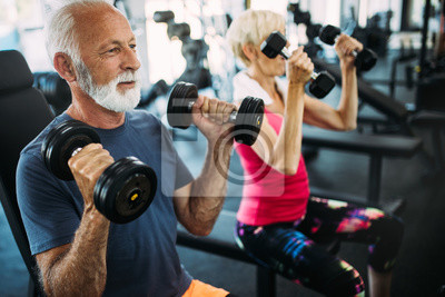 Fototapeta Mature fit couple exercising in gym to stay healthy