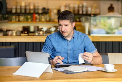 Fototapeta Mature new small business owner calculating online restaurant bill expenses and taxes