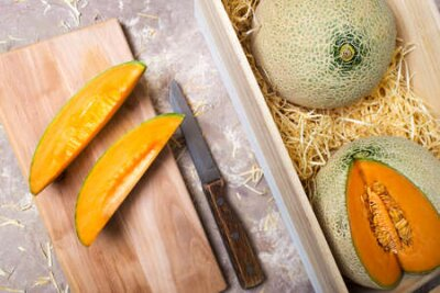 Fototapeta melons in a wooden box in straw. pieces of melon with a knife on the board.