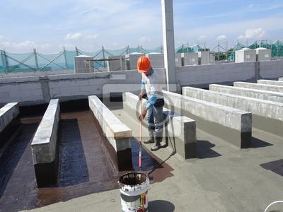 Fototapeta Membrana hydroizolacyjna stosowana przez pracowników budowlanych na płycie betonowej. Warstwa hydroizolacyjna zapobiegająca przedostawaniu się wody pod płytę betonową.