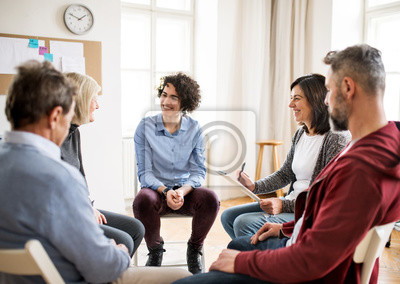 Fototapeta Men and women sitting in a circle during group therapy, talking.