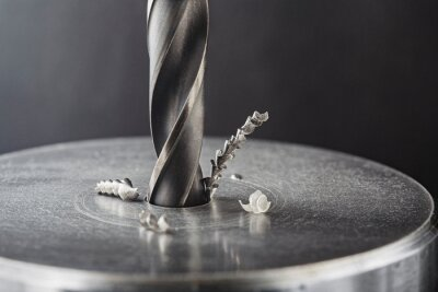 Fototapeta metal drill bit make holes in steel billet on industrial drilling machine. Metal work industry. multi cutting tool and end mill.