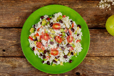 Fototapeta Mexican salad with rice, tomato, avocado corn and beans