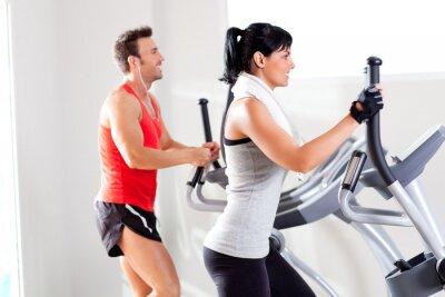 Fototapeta mężczyzna i kobieta z eliptycznego orbitrek na siłowni