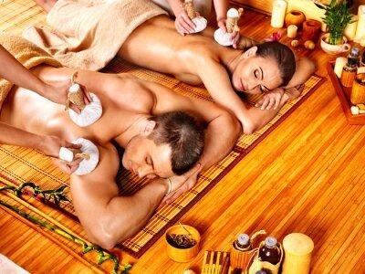 Mężczyzna i kobieta zaczyna ziołowy piłka masażu w spa.