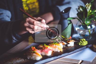 Fototapeta Mężczyzna jedzenia sushi zestaw z pałeczki w restauracji