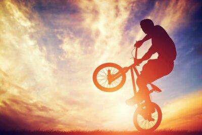 Fototapeta Mężczyzna jedzie na bmx rower wykonywania trick przed zachodem słońca niebo