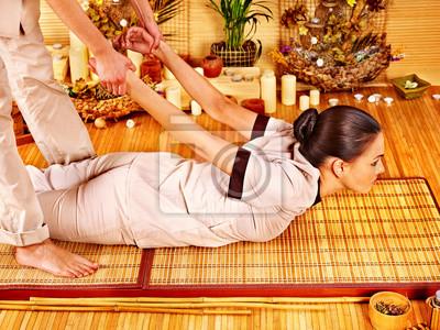 Mężczyzna masażysta robi masaż kobieta w bambusa spa.